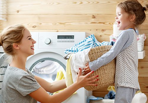 "A mom and daughter remove clean, soft laundry from the dryer with the caption ""Clean Water for Your Whole Home""."