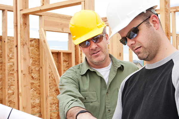 Construction managers review plans for a new home in progress.