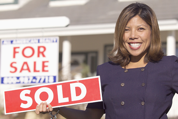 """A real estate agent shows off a """"SOLD"""" sign after selling a new home."""