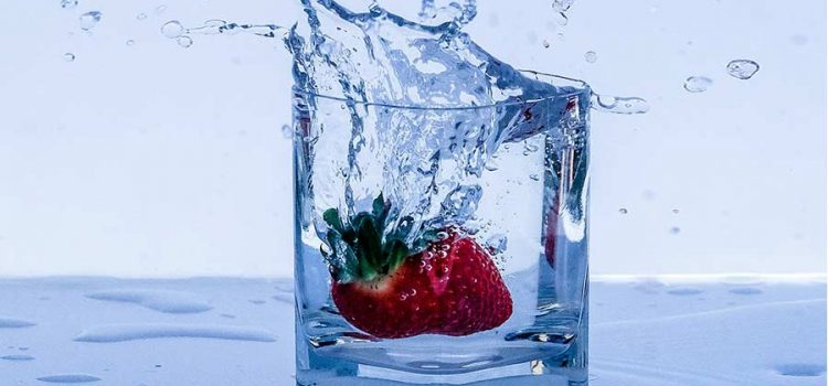 Glass of purified water with a strawberry