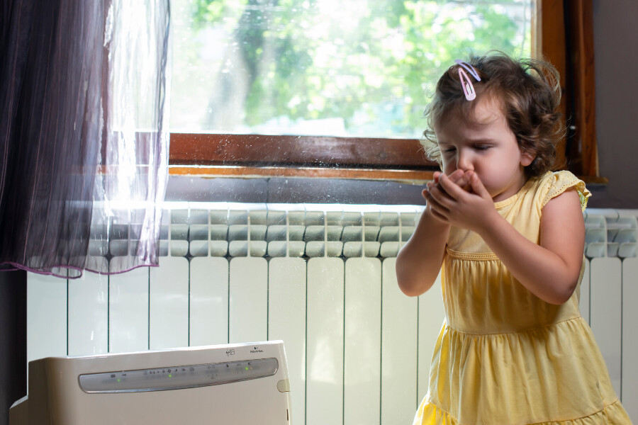 A little girl coughing and sneezing in her home due to poor indoor air quality.